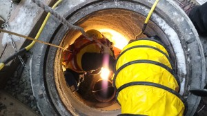 Looking down into a catch basin where a worker is cleaning debris from the basin's inlet.